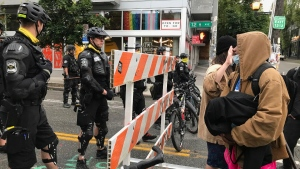 A protester stands with her hand up in front of a road blocked by Seattle police in the Capitol Hill Organized Protest zone, on July 1, 2020. (Aron Ranen / AP)
