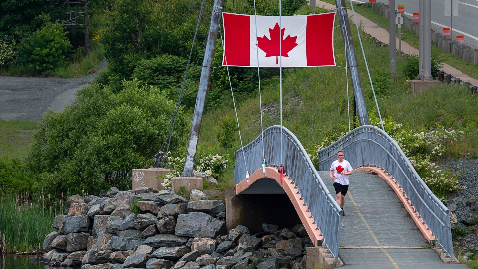 A runner heads over the Fraser Conrad Bridge that spans Lake Banook in Dartmouth, N.S. on Canada Day, Wednesday, July 1, 2020. THE CANADIAN PRESS/Andrew Vaughan