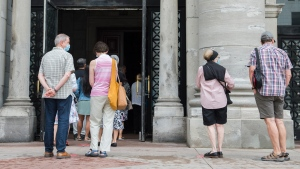People wait to attend mass at the Mary Queen of the World Cathedral in Montreal, Sunday, June 28, 2020, as the COVID-19 pandemic continues in Canada and around the world. THE CANADIAN PRESS/Graham Hughes