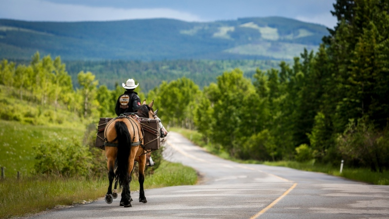 Felipe Masetti, a Brazilian cowboy who has been riding from Alaska to Calgary and who has also been chosen as the parade marshal for the Calgary Stampede, rides his pony Smokey as pack pony Mack follows along near Waiparous Village, Alta. (Jeff McIntosh/The Canadian Press)