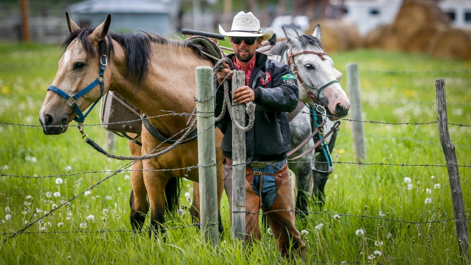 Felipe Masetti, a Brazilian cowboy who has been riding from Alaska to Calgary and who has also been chosen as the parade marshal for the Calgary Stampede, rides his pony Smokey as pack pony Mack follows along near Waiparous Village. (Jeff McIntosh/The Canadian Press)