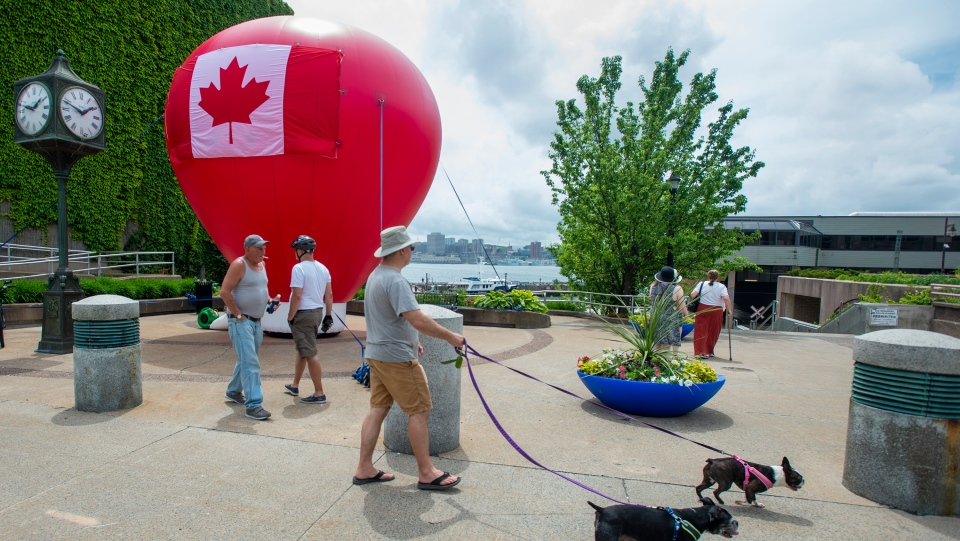Pedestrians stroll past a large inflated balloon on the waterfront in Dartmouth, N.S. on Canada Day, Wednesday, July 1, 2020. THE CANADIAN PRESS/Andrew Vaughan