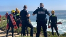 Santa Cruz police officers on the shoreline of the Pacific Ocean after a vehicle drove off the cliff and into the water. (Santa Cruz Police/Twitter)
