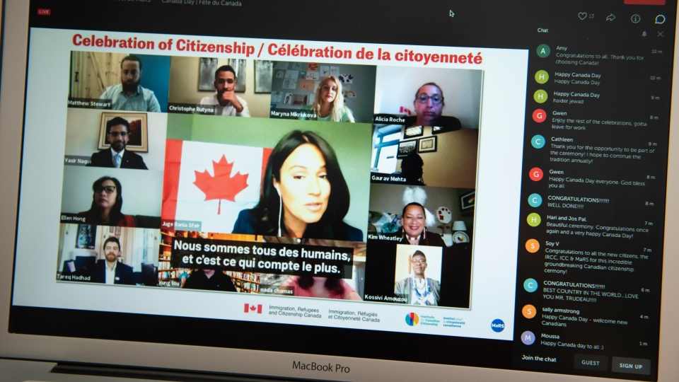 Citizenship Judge Rania Sfeir, centre, speaks to new Canadian citizens during a virtual citizenship ceremony held over livestream due to the COVID-19 pandemic, on Canada Day, Wednesday, July 1, 2020, seen on a mobile phone in Ottawa. THE CANADIAN PRESS/Justin Tang