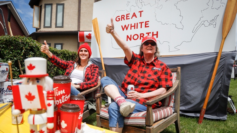 Linda Myers and her daughter Riley Myers wave to cars from in front of their Canada Day decorated house on Canada Day in Airdrie, Alta., Wednesday, July 1, 2020.THE CANADIAN PRESS/Jeff McIntosh