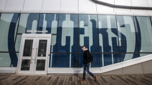 A pedestrian walks outside Rogers Place, home of the Edmonton Oilers, in Edmonton, Alta., on Thursday March 12, 2020. Alberta is upping the ante in its bid for Edmonton to co-host the NHL's summer Stanley Cup playoff tournament, pitching Rocky Mountain excursions for players' families. THE CANADIAN PRESS/Jason Franson
