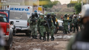 Members of the national guard walk near an unregistered drug rehabilitation center in Irapuato, Mexico, Wednesday, July 1, 2020, after gunmen burst into the facility and opened fire. (AP Photo/Mario Armas)