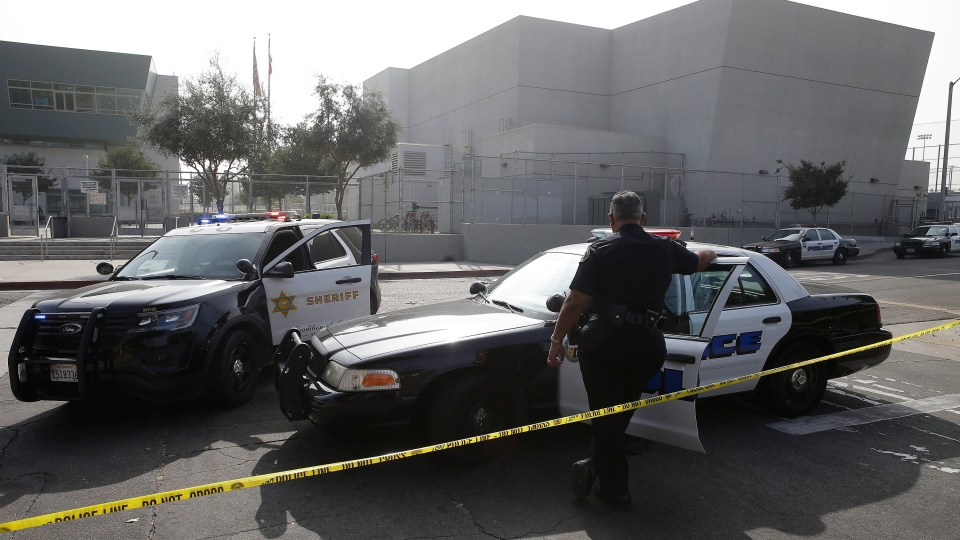 Los Angeles Sheriffs officers and Los Angeles Unified School District police officers guard the campus of Esteban Torres High School in unincorporated East Los Angeles, after a sheriff's deputy fatally shot a man wielding a sword, after he had climbed over the fence to get onto the school grounds Wednesday, Nov. 13, 2019. On Tuesday, June 30, 2020, the Los Angeles Unified School District voted an immediate 35% cut to the budget of its school police. (AP Photo/Damian Dovarganes, File)