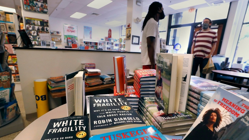"In this Wednesday, June 24, 2020, photograph, books are displayed, including ""The Tuskegee Airmen,"" and ""White Fragility,"" at the Black-owned Frugal Bookstore in the Roxbury neighborhood of Boston. (AP Photo/Charles Krupa)"