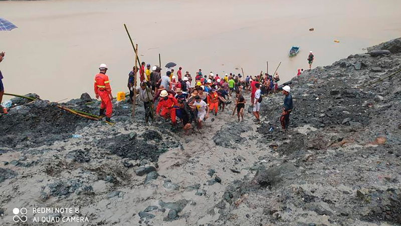 In this photo released from Myanmar Fire Service Department, rescuers carry a recovered body of a victim in a landslide from a jade mining area in Hpakant, Kachine state, northern Myanmar Thursday, July 2, 2020. (Myanmar Fire Service Department via AP