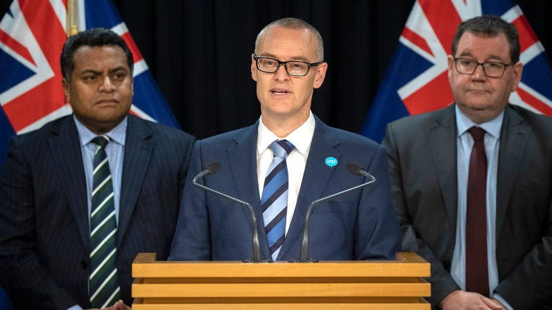 New Zealand Health Minister David Clark, center, flanked by Cabinet colleagues Grant Robertson, right, and Kris Faafoi addresses a press conference where he announced his resignation at parliament in Wellington, New Zealand Thursday, July 2, 2020. (Mark Mitchell/New Zealand Herald via AP)