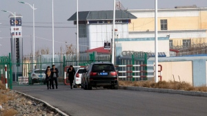 In this Dec. 3, 2018, file photo, people walk by a police station by the front gate of the Artux City Vocational Skills Education Training Service Center in Artux in western China's Xinjiang region. (AP Photo/Ng Han Guan, File)