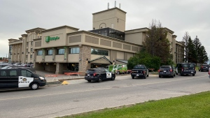 Six CPS vehicles outside of the Holiday Inn on McKinnon Dr. N.E. following a shooting Thursday morning that left one person injured