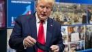 U.S. President Donald Trump holds his protective face mask as he speaks while touring Ford's Rawsonville Components Plant that has been converted to making personal protection and medical equipment, May 21, 2020, in Ypsilanti, Mich. (AP Photo/Alex Brandon)