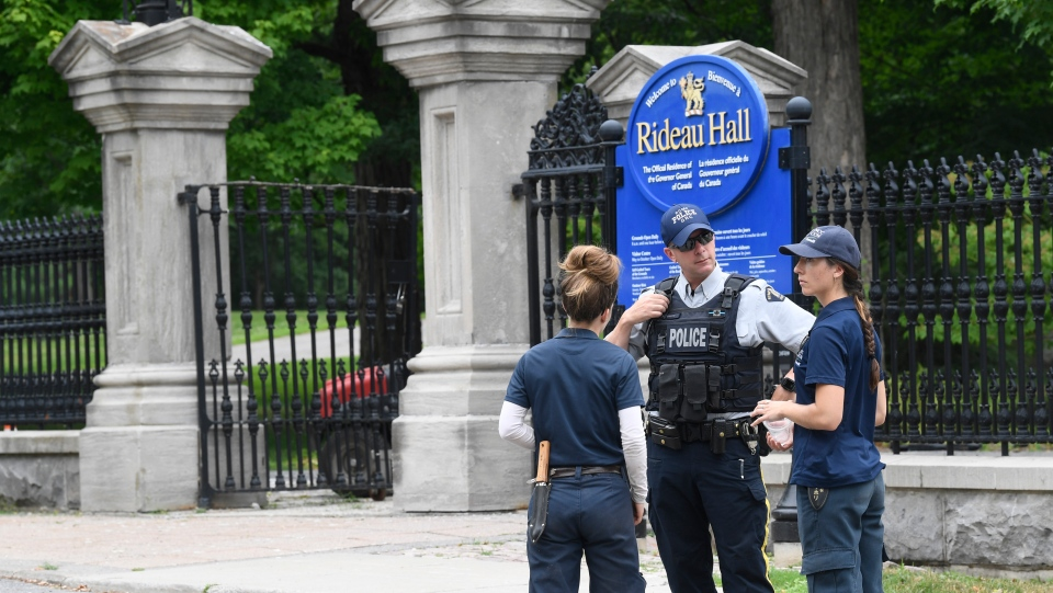 An RCMP officer talks with National Capital Commission employees who were trying to get to work, outside Rideau Hall in Ottawa on Thursday, July 2, 2020. The RCMP say they have safely resolved an