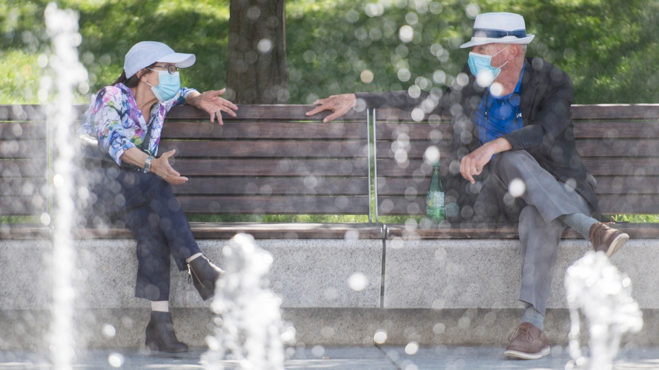 People wear face masks as they talk on a city bench in Montreal  as the COVID-19 pandemic continues in Canada and around the world. THE CANADIAN PRESS/Graham Hughes