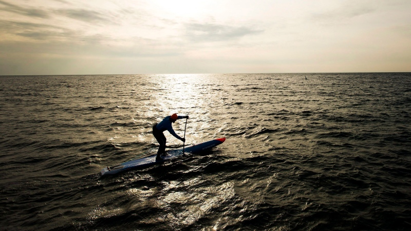 Olympic gold medallist in 1984 Larry Cain, 53, stand up paddles in the frigid cold temperatures on Lake Ontario in Oakville, Ont., on Tuesday, December 13, 2016. (THE CANADIAN PRESS/Nathan Denette)