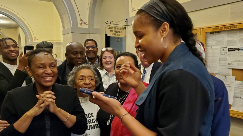 Maya Moore, right, calls Jonathan Irons as supporters react in Jefferson City on March 9, 2020, after Cole County Judge Dan Green overturned Irons' convictions in a 1997 burglary and assault case. (Jeff Haldiman / The Jefferson City News-Tribune via AP, File)