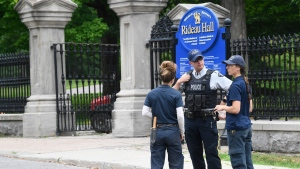 An RCMP officer talks with National Capital Commission employees who were trying to get to work, outside Rideau Hall in Ottawa on Thursday, July 2, 2020. THE CANADIAN PRESS/Adrian Wyld