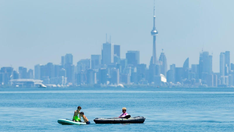People enjoy activities on Lake Ontario overlooking the City of Toronto skyline during the COVID-19 pandemic at Jack Darling Park in Mississauga, Ont., on Wednesday, June 17, 2020. THE CANADIAN PRESS/Nathan Denette