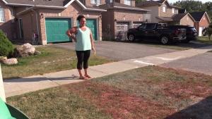 Erin Van Kessel standing beside her daughter's artwork outside their north-end Barrie home July 2, 2020.