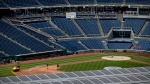 Solar panels on top of a parking garage are visible as workers water the infield at Washington Nationals Stadium, Wednesday, July 1, 2020, in Washington. (AP Photo/Andrew Harnik)