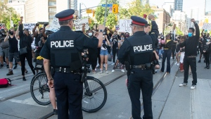 Police officers look on as protesters march in an anti-racism rally in Toronto on Saturday, June 6, 2020. (THE CANADIAN PRESS/Chris Young)