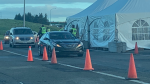Vehicles wait in line at the border between Nova Scotia and New Brunswick on the first morning of the Atlantic Canadian bubble.