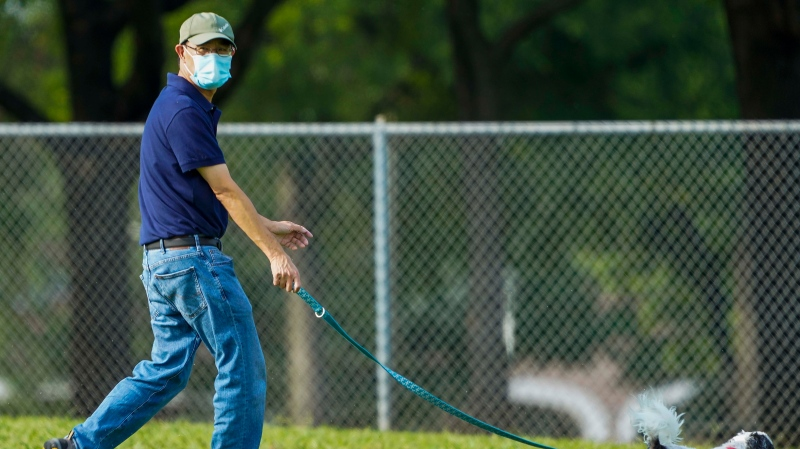 Jeff Ho wears a face mask while walking his dog at Custer Park on Thursday, July 2, 2020, in Richardson, Texas. (Smiley N. Pool/The Dallas Morning News via AP)