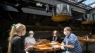 Patrons sit on the patio as waitress Paulina Pasierbek, left, takes orders at Joey Sherway, part of the Joey Restaurant chain during the COVID-19 pandemic in Toronto on Wednesday, June 24, 2020. Toronto and the GTA entered stage two of opening. THE CANADIAN PRESS/Nathan Denette