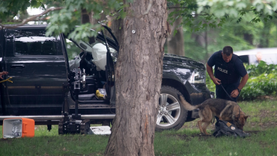 An RCMP officer works with a police dog as they move through the contents of a pick up truck on the grounds of Rideau Hall in Ottawa, on July 2, 2020. (THE CANADIAN PRESS / Adrian Wyld)