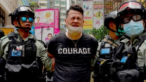 Police detain a pepper-sprayed protester in Causeway Bay before the annual handover march in Hong Kong, on July 1, 2020. (Vincent Yu / AP)