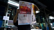 """A worker checks a copy of Apple Daily's July 1, 2020, edition seen with its front page title of """"Draconian law is effective, one country two system is dead"""" at the newspaper's printing house in Hong Kong, Wednesday, July 1, 2020. (AP Photo/Vincent Yu)"""