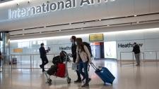 In this Monday, June 8, 2020 file photo, passengers wearing face masks arrive at London's Heathrow Airport. (AP Photo/Matt Dunham, File)