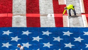 Wyndham Hotels workers Jeremy Franklin and Steve Ratier, bottom left, stencil stars as they and members of a painting crew create a giant U.S. flag across the front lawn of the Hotel Galvez in Galveston, Texas, Wednesday, July 1, 2020. (Stuart Villanueva/The Galveston County Daily News via AP)