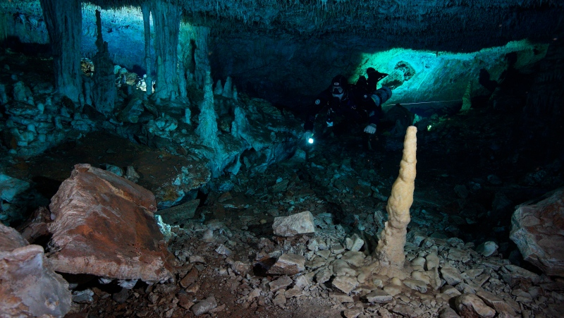 "This Dec. 12, 2019 photo released by CINDAQ.ORG shows a diver in the ""La Mina Roja"" passage of the Sagitario underwater cave system near Playa del Carmen in Mexico's Yucatan Peninsula.  (CINDAQ.ORG via AP)"