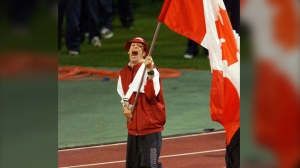 Canadian flag bearer Gary Longhi reacts as he carries his country's flag during the opening ceremony of the Paralympic Games in Sydney Wednesday October 18, 2000. Gary Longhi, a four-time Paralympian and Canada's flag-bearer for the opening ceremonies of the 2000 Sydney Paralympics, has died at the age of 56. THE CANADIAN PRESS/AP, Rob Griffith