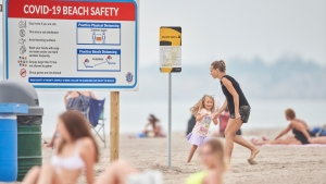 Large signs for COVID-19 beach safety are prominently displayed at the beach in Port Stanley, Ont., on Monday, June 22, 2020. Beaches in Southwestern Ontario opened for the first time on Monday after being closed due COVID-19 restrictions. Attendance was low on the first morning but overcast weather and threat of thunder storms was not conducive to enticing large crowds. THE CANADIAN PRESS/Geoff Robins