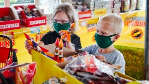 Children wear face masks as they pick out fireworks at Wild Willy's Fireworks tent in Omaha, Neb., Monday, June 29, 2020, ahead of the 4th of July holiday, (AP Photo/Nati Harnik)