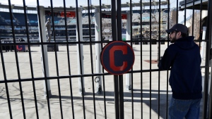 FILE - In this March 26, 2020, file photo, Jason Hackedorn looks into Progressive Field, home of the Cleveland Indians baseball team, in Cleveland. (AP Photo/Tony Dejak, File)