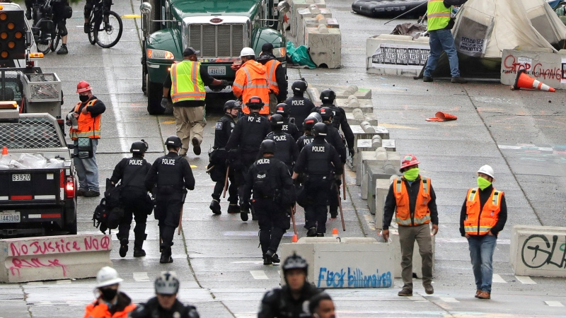 Police and city workers fill a street occupied hours earlier by an encampment of protesters Wednesday, July 1, 2020, in Seattle, where streets had been blocked off in an area demonstrators had occupied for weeks. (AP Photo/Elaine Thompson)