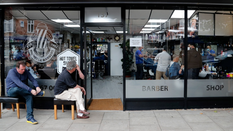 People queue outside a Barber shop as it opens for the first time after the COVID-19 lockdown in London, Saturday, July 4, 2020. (AP Photo/Frank Augstein)