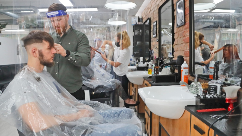 A barber cuts hair at Northfields Barber as it opens for the first time after the COVID-19 lockdown in London, Saturday, July 4, 2020. (AP Photo/Frank Augstein)