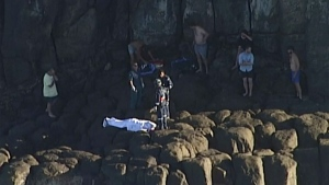 In this image from a video, the covered body is placed at the bottom of a cliff near Indian Head, Australia Saturday, July 4, 2020. A 20-year-old scuba diver died Saturday after being attacked by a shark off the coast of Australia's Queensland state, authorities said. (AuBC/CHANNEL 7/CHANNEL 9 via AP)
