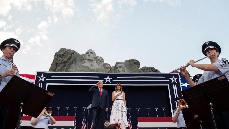 U.S. President Donald Trump, accompanied by first lady Melania Trump, stands during the national anthem with a flyover by the U.S. Navy Blue Angles at Mount Rushmore National Memorial, July 3, 2020, near Keystone, S.D. (AP Photo/Alex Brandon)