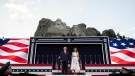 U.S. President Donald Trump, accompanied by first lady Melania Trump, stand during a flyover at Mount Rushmore National Memorial, Friday, July 3, 2020, near Keystone, S.D. (AP Photo/Alex Brandon)