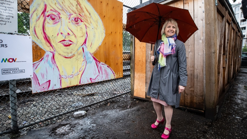 British Columbia provincial health officer Dr. Bonnie Henry wears a pair John Fluevog shoes designed in her honour, as she views her image at the Murals of Gratitude exhibition in Vancouver, on Friday, July 3, 2020. The business improvement association in Vancouver's Gastown neighbourhood honoured Dr. Henry on Friday with a sneak peek at a mural exhibition featuring her image. THE CANADIAN PRESS/Darryl Dyck