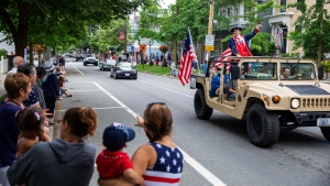 Spectators watch as a Fourth of July parade passes Saturday, July 4, 2020, in Bristol, R.I. (AP Photo/David Goldman)