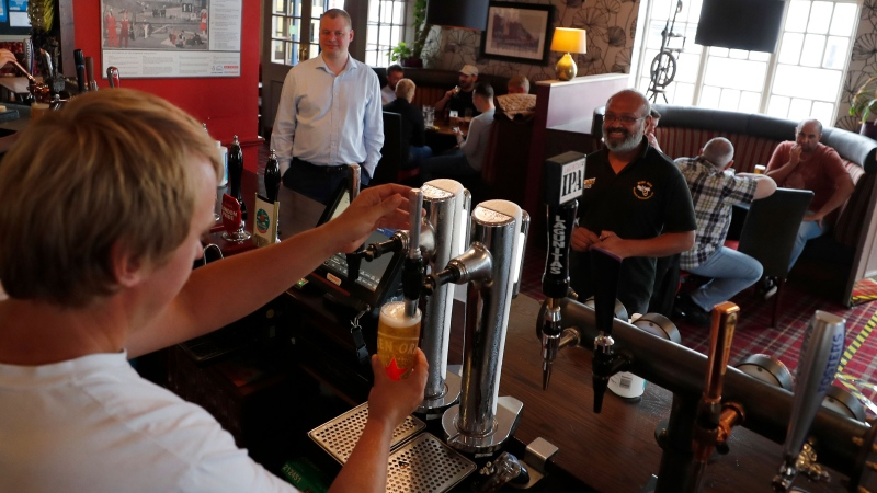 A bar man pulls a beer at the Chandos Arms pub in London, Saturday, July 4, 2020. England is embarking on perhaps its biggest lockdown easing yet as pubs and restaurants have the right to reopen for the first time in more than three months. In addition to the reopening of much of the hospitality sector, couples can tie the knot once again, while many of those who have had enough of their lockdown hair can finally get a trim. (AP Photo/Frank Augstein)