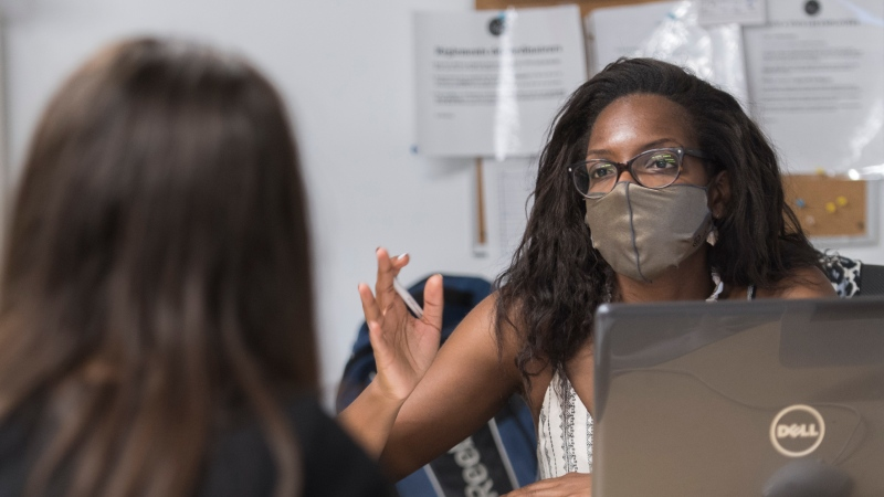 Labour standards lawyer Farah Rousseau speaks to a woman at a legal clinic for victims of racism in Montreal, Saturday, July 4, 2020. THE CANADIAN PRESS/Graham Hughes
